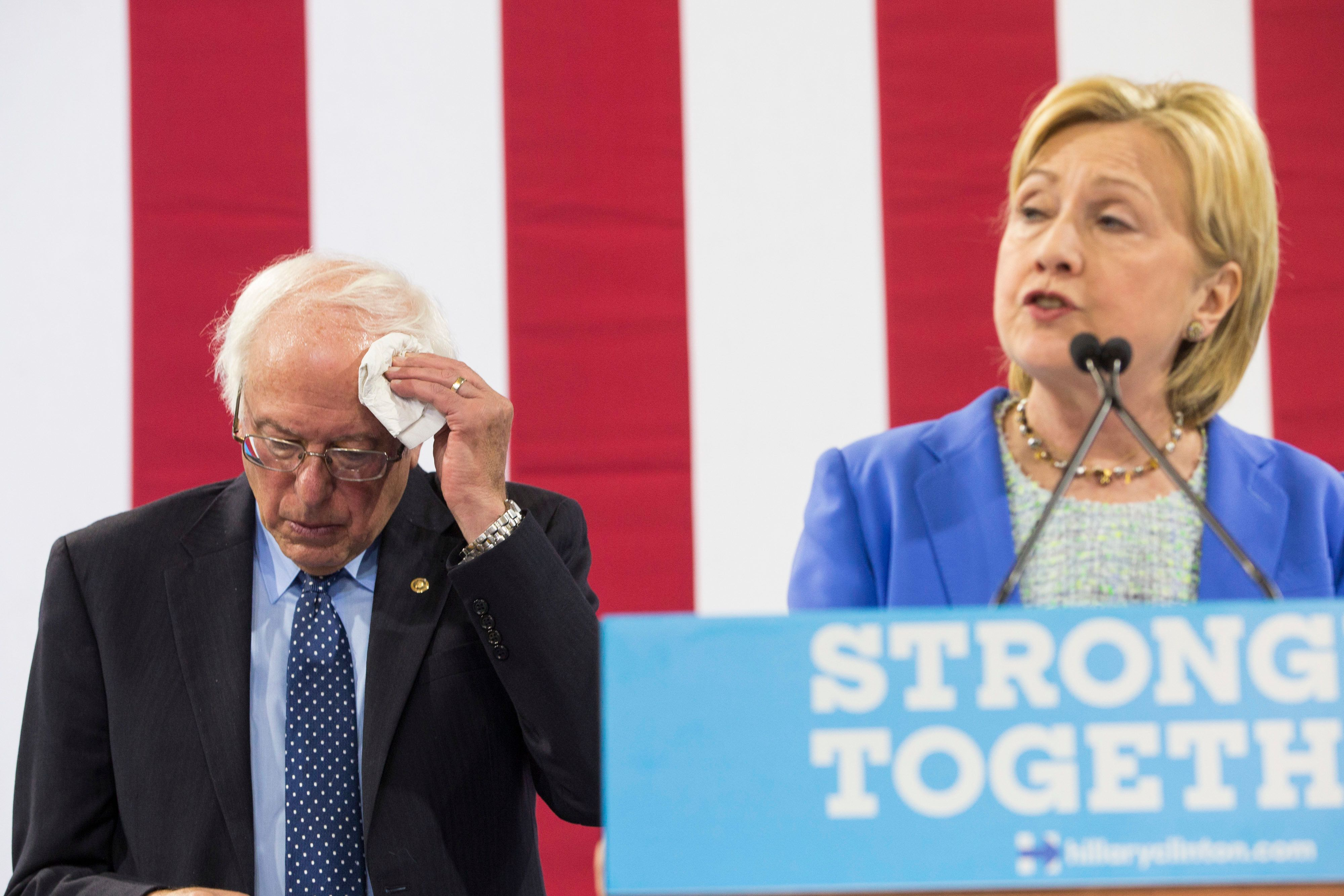 PORTSMOUTH, NH - JULY 12:  U.S. Senator and former presidential candidate Bernie Sanders wipes his forehead  as U.S. Democratic Presidential candidate Hillary Clinton speaks at a campaign event where Sanders endorsed Clinton in Portsmouth, N.H., July 12, 2016. (Photo by Keith Bedford/The Boston Globe via Getty Images)
