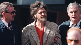 Theodore Kaczynski is led into federal court where he was charged with a single federal weapons violation April 4. Officials suspect Kaczynski of being the Unabomber, following a search of his home.  ?? OUT