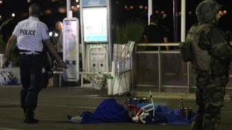 A police officer and a soldier stand next to a dead body covered with a blue sheet on the Promenade des Anglais seafront in the French Riviera town of Nice on July 15, 2016, after a van drove into a crowd watching a fireworks display. At least 75 people were killed when a truck drove into a crowd watching a fireworks display in the French resort of Nice, a lawmaker said on July 15. / AFP / VALERY HACHE        (Photo credit should read VALERY HACHE/AFP/Getty Images)
