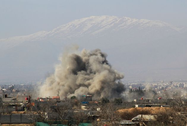 Smoke rises over Darayya after government forces drop barrel bombs on the community, according to