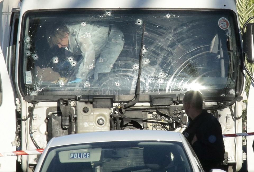 Forensic police investigate the truck that plowed through a crowd celebrating Bastille Day onthe Promenade des Anglais
