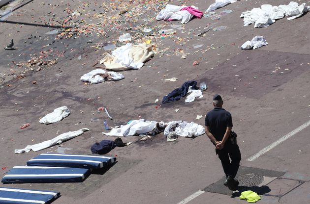 French gendarmes walk past clothes and mattresses at the site of the deadly