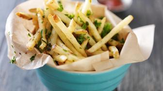 truffle fries standing up in a bowl with wax paper lining shot close up