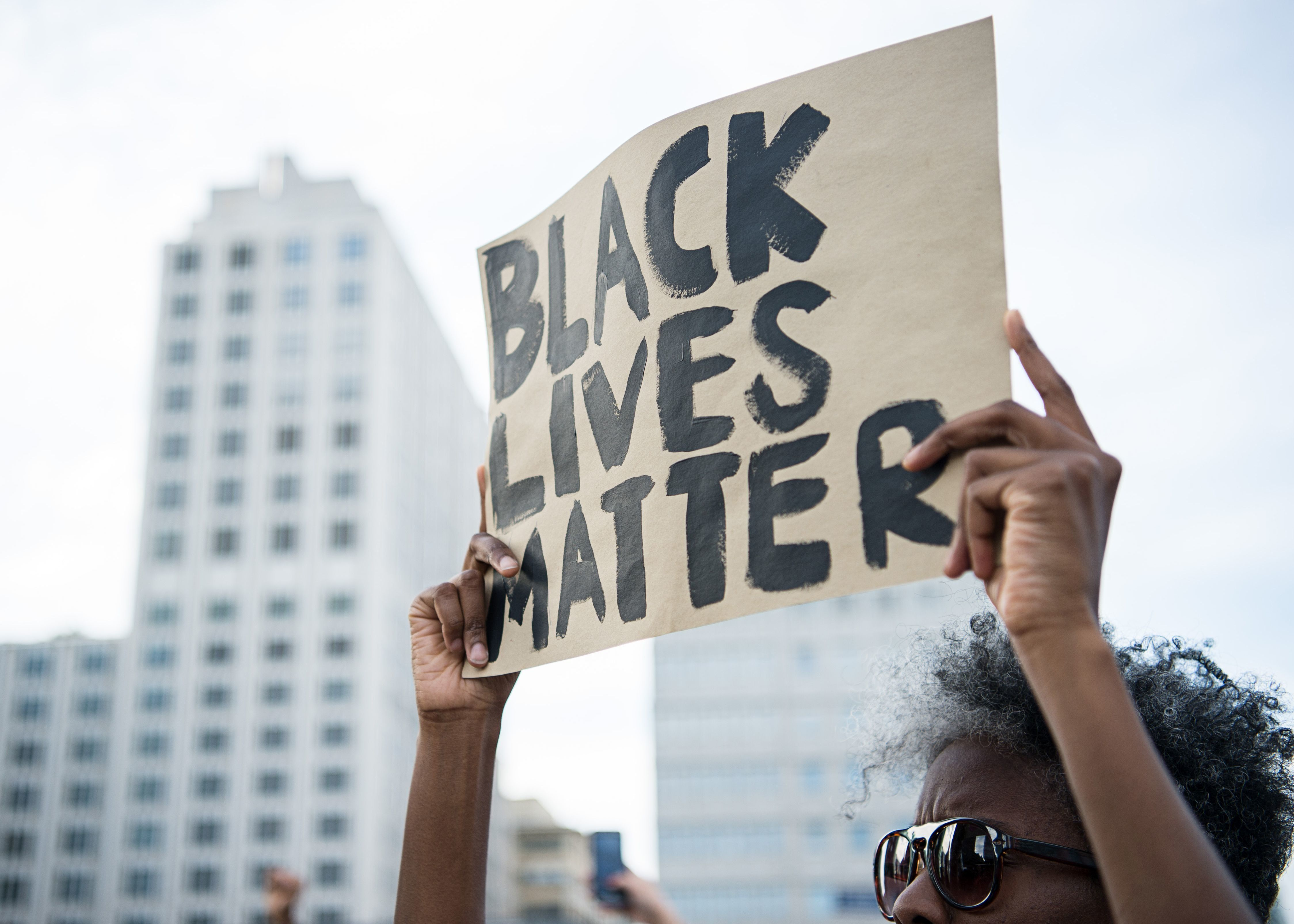 A protestor holds up a sign reading 'Black Lives Matter' during a demonstration in Berlin, on July 10, 2016 with the motto 'Black Lives Matter - No Justice = No Peace' as protest over the deaths of two black men at the hands of police last week. / AFP / dpa / Wolfram Kastl / Germany OUT        (Photo credit should read WOLFRAM KASTL/AFP/Getty Images)