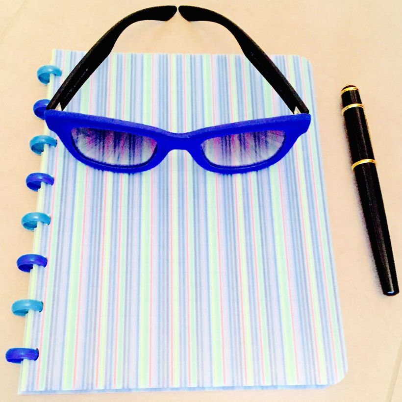 Exceptional spectacles on a notebook near pen