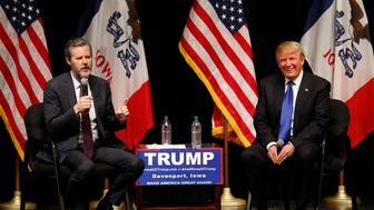 Republican presidential candidate Donald Trump, right, talks with Jerry Falwell Jr., during a campaign event at the Adler Theater, Saturday, Jan. 30, 2016 in Davenport, Iowa. (AP Photo/Paul Sancya)
