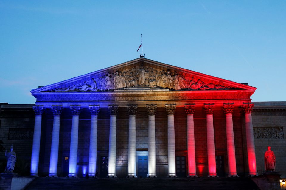 A picture taken on July 15, 2016 shows the French National Assembly illuminated with the colors of the French National flag i