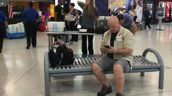 Traveler Chris Sassi of New York checks his phone for updates while awaiting news on his flight to Istanbul.