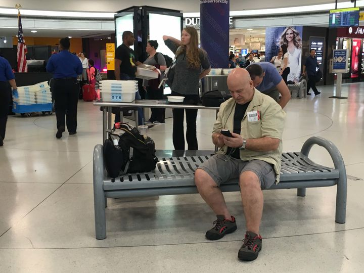 Chris Sassi of New York checks his phone for updates while awaiting news on his flight to Istanbul.