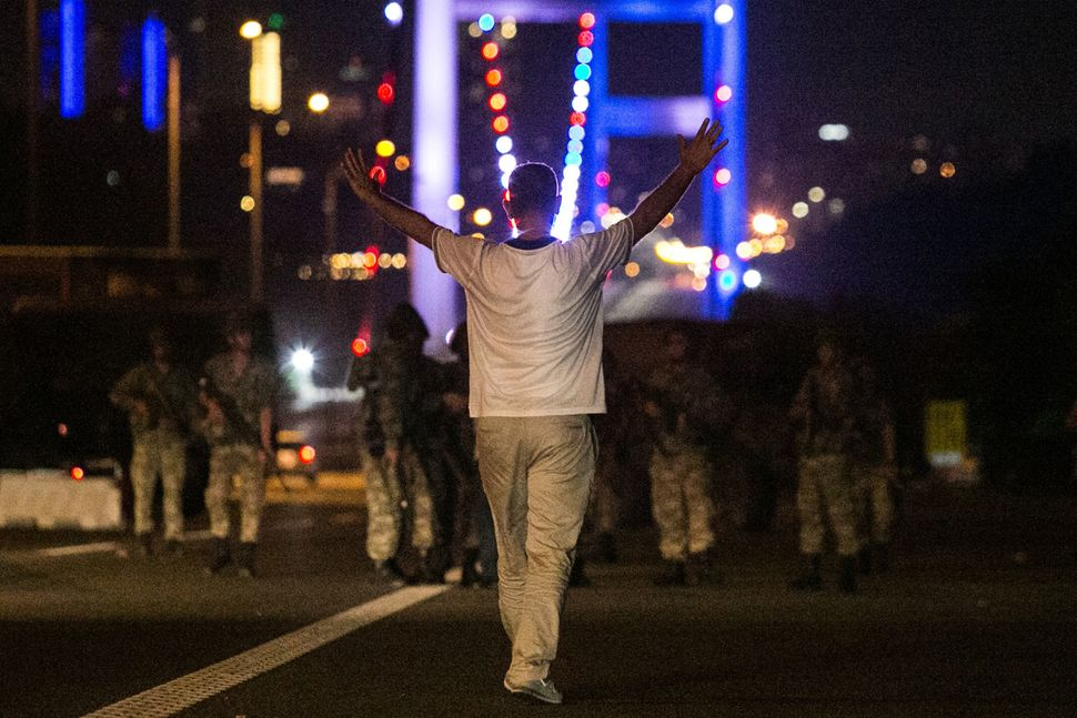 A man approaches Turkish military with his hands up at the entrance to the Bosphorus bridge in Istanbul.