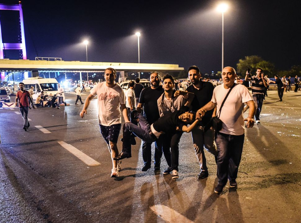 People carry a man shot during clashes with Turkish military at the entrance to the Bosphorus bridge in Istanbul.