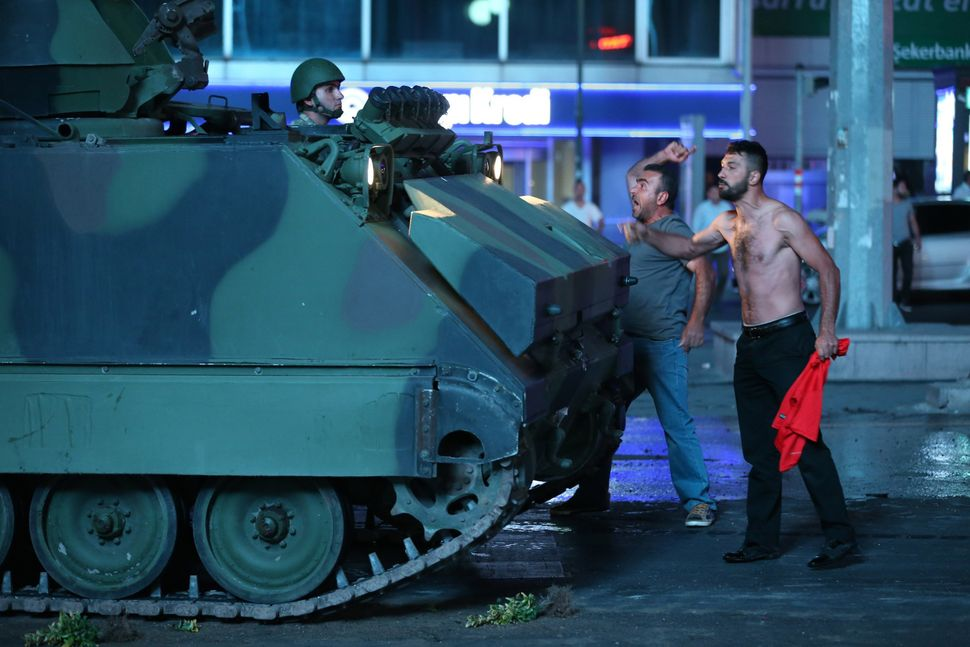 People stand in the way of a tank in the streets of Ankara, Turkey, on Friday night. Turkey's armed forces sai