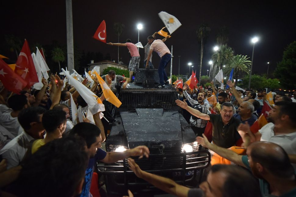 People climb aboard an armored vehicle in Mersin.