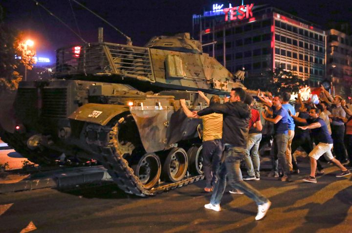 People in Turkey swarm a tank in the streets amid an attempted military coup.