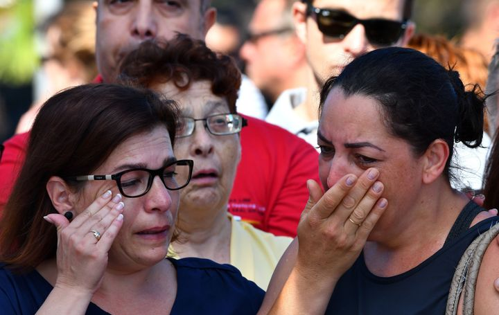 Mourners in Nice, France weep after a terrorist attacked a crowd of people celebrating a national holiday, killing