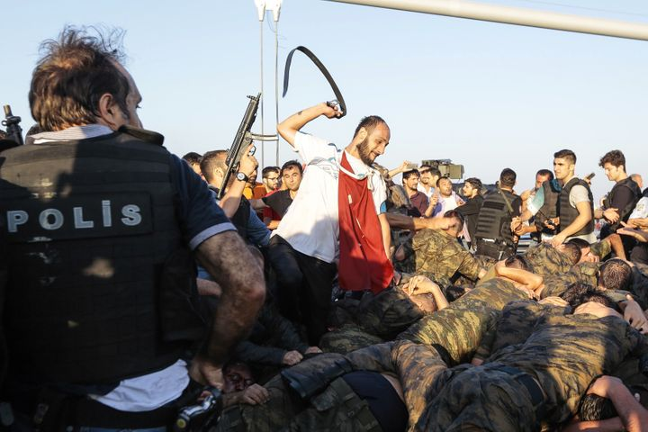 An unidentified man uses his belt to hit Turkish soldiers on Istanbul's Bosphorus bridge who were allegedly involved in