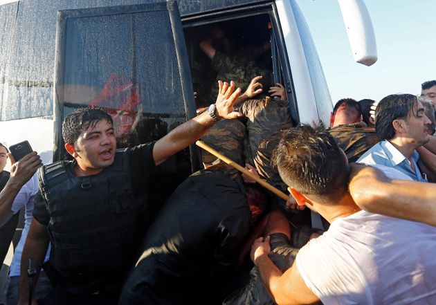 A policeman protects soldiers from the mob after troops involved in the coup surrendered on the Bosphorus