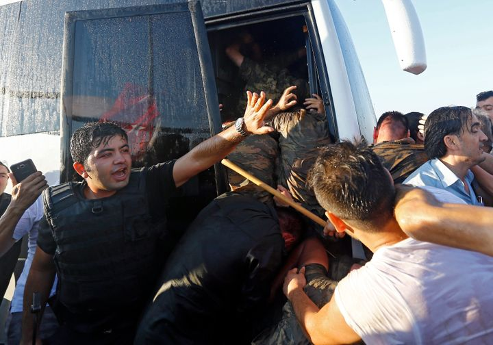 A policeman protects soldiers from the mob after troops involved in the coup surrendered on the Bosphorus Bridge.