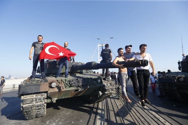 People pose near a tank after troops involved in the coup surrendered on the Bosphorus Bridge in