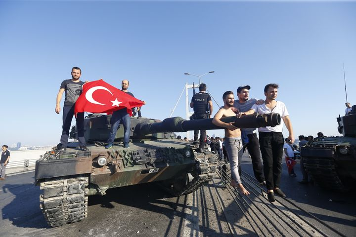 People pose near a tank after troops involved in the coup surrendered on the Bosphorus Bridge in Istanbul.