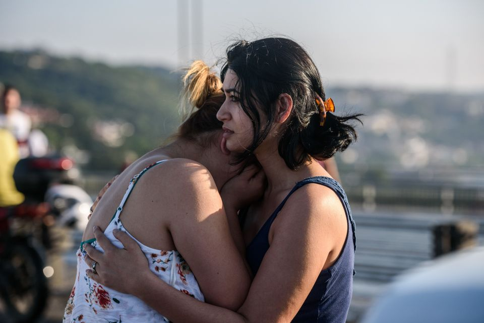 Women embrace after people took over military position on the Bosphorus bridge.