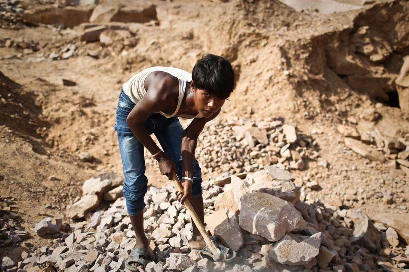 <i>A teenage boy breaks rocks at a quarry in India</i>
