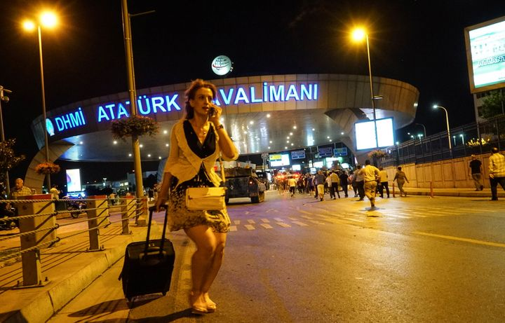 A passenger walks as armytanks enter the Ataturk Airport on July 16, 2016, in Istanbul, Turkey. Istanbul's bridges acro