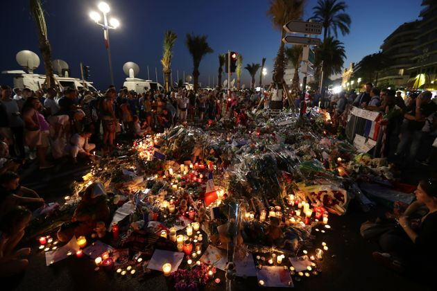 Crowds gather at a memorial on the Promenade des Anglais in