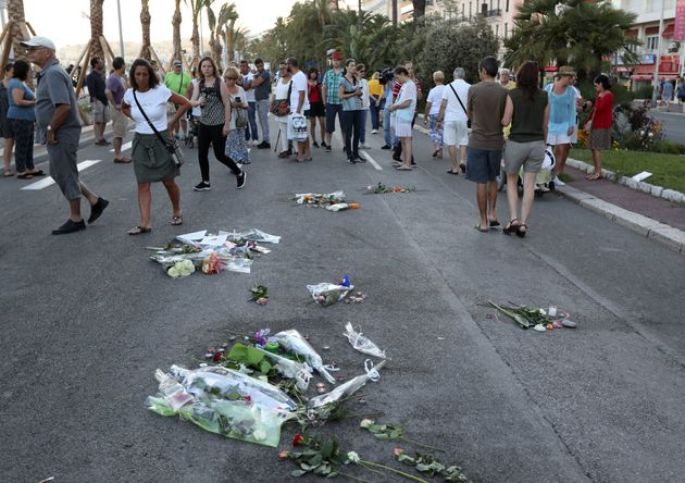 People pass flowers and messages left in the road for victims of the deadly Bastille Day