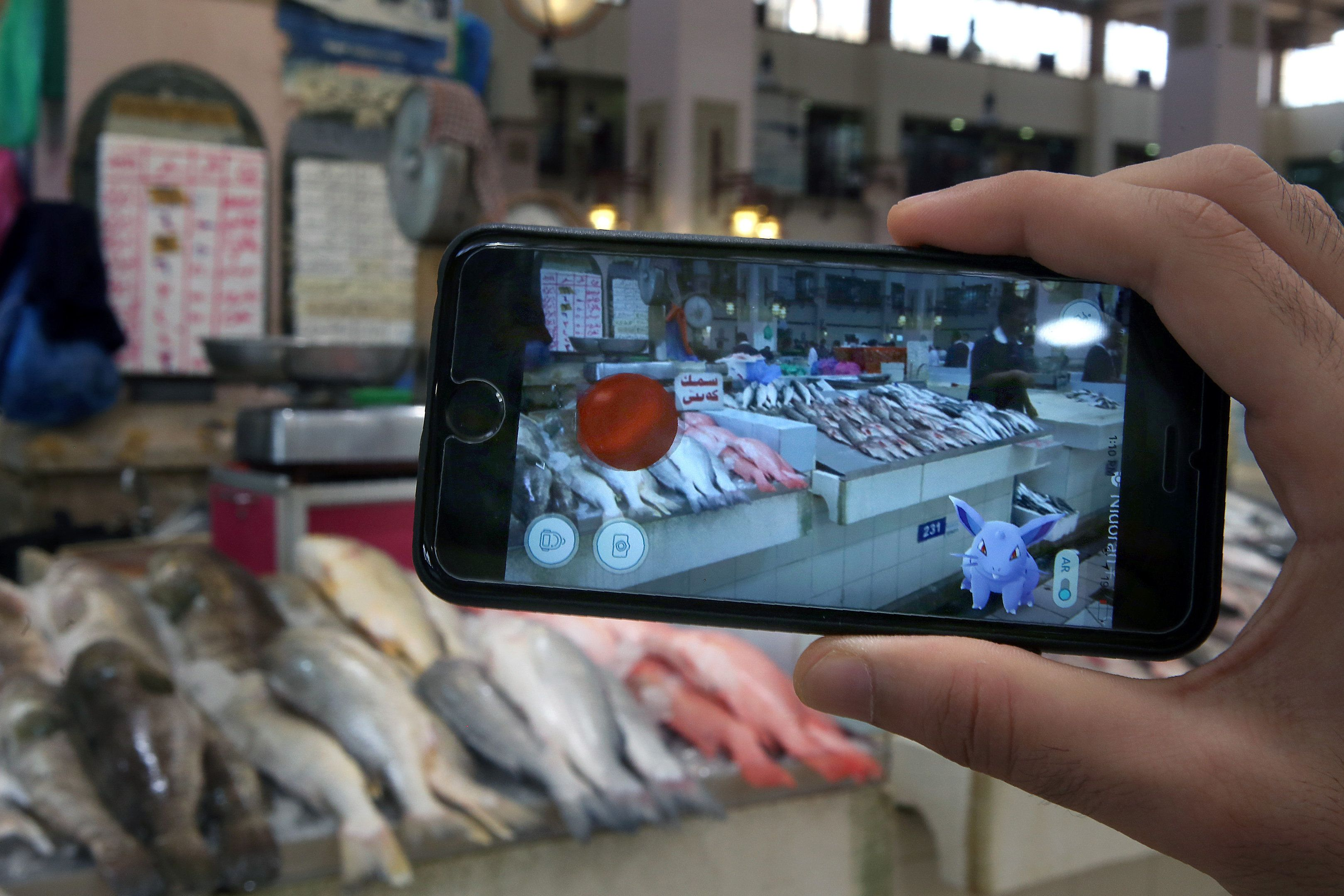 A gamer uses the Pokemon Go application on his mobile in the main fish market in Kuwait City on July 14, 2016.   / AFP / YASSER AL-ZAYYAT        (Photo credit should read YASSER AL-ZAYYAT/AFP/Getty Images)