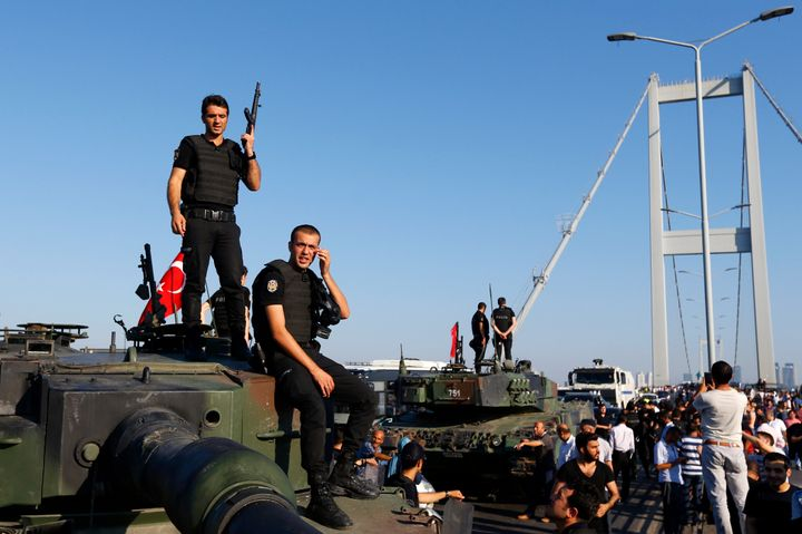 Policemen stand atop military armored vehicles after troops involved in the coup surrendered on the Bosphorus Bridge in Istan