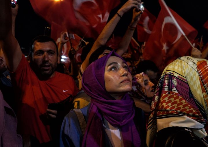 A woman looks up during a pro-government rally in central Istanbul's Taksim square, Saturday, July 16, 2016.