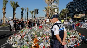 A police officer watches people gathering around a floral tribute for the victims killed during a deadly attack, on the famed Boulevard des Anglais in Nice, southern France, Sunday, July 17, 2016. French authorities detained two more people Sunday in the investigation into the Bastille Day truck attack on the Mediterranean city of Nice that killed at least 84 people, as authorities try to determine whether the slain attacker was a committed religious extremist or just a very angry man. (AP Photo/Laurent Cipriani)