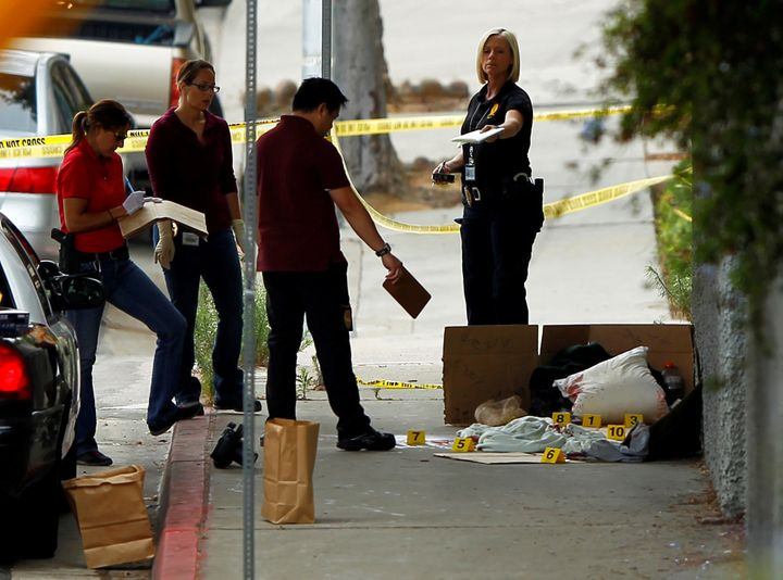 Police investigate Friday's scene under a San Diego highway overpass where another apparent attack by a serial killer targeti