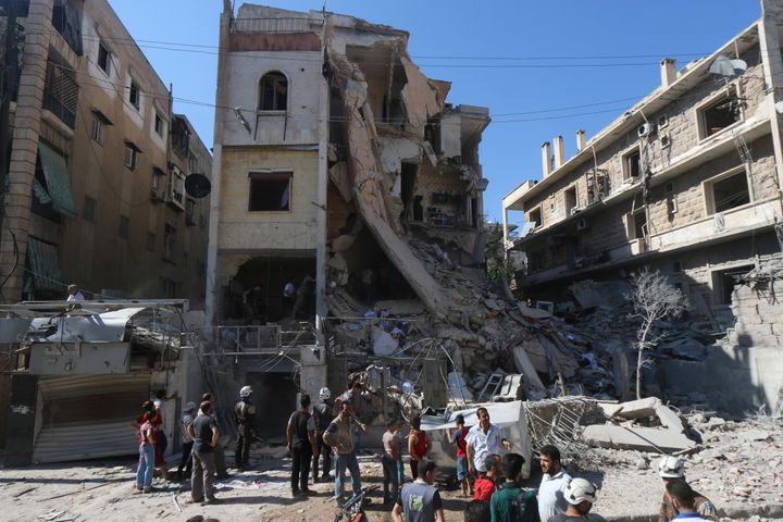 Men look for survivors inside a damaged building after an airstrike on Aleppo's rebel held Saif al-Dawla district, Syria July