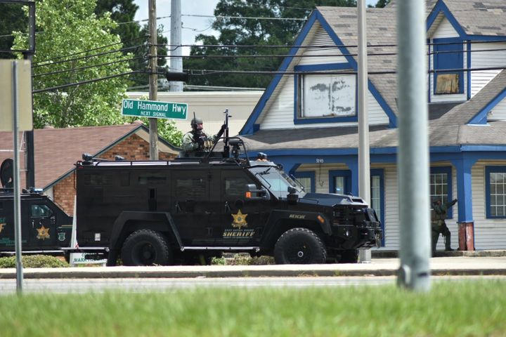 Officers with the East Baton Rouge Sheriff's Office search an area nearthe Hammond Aire Plaza, where Sunday's shooting