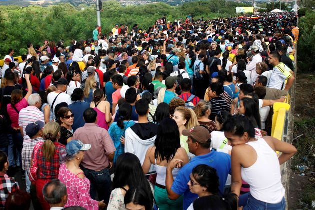 People cross over the Simon Bolivar international bridge to Colombia to take advantage of the temporary...