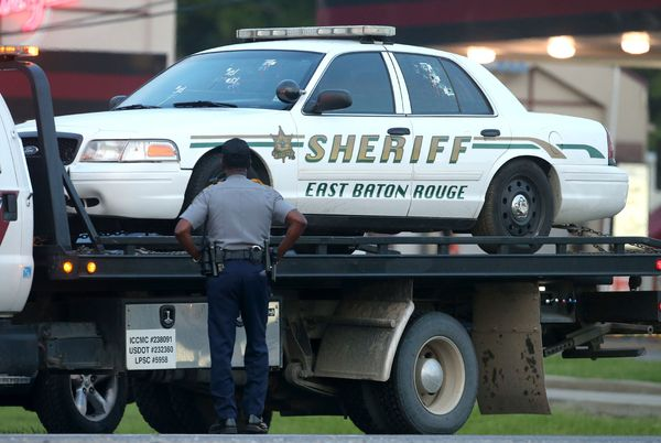 A police officer stands in front of an East Baton Rouge police car with bullet holes as it's towed away.