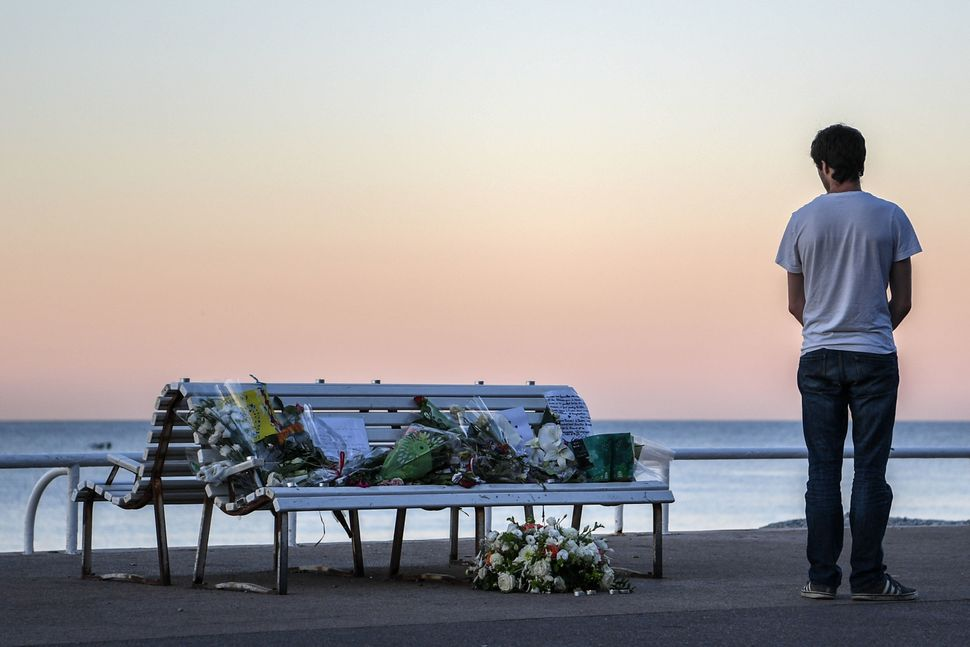 A man looks at a floral tribute.