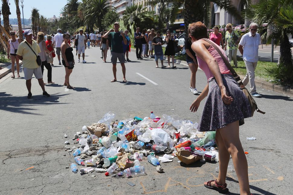 People throw garbage at the site where Mohamed Lahouaiej Bouhlel was killed by the police.