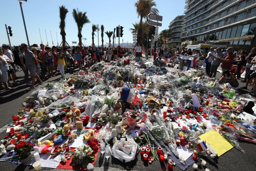 People gather near flowers placed at a makeshift memorial near the Promenade des Anglais.