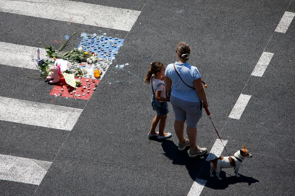 A woman and child stand near a makeshift memorial placed on the road.