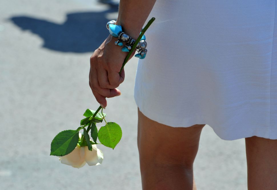 A woman holds a rose ahead of the minute of silence.