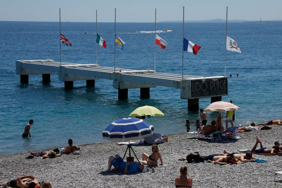 Flags fly at half-mast on a pier near the Promenade des Anglais.