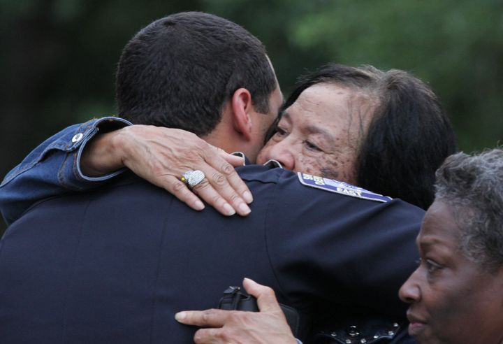 A police officer is embraced after a vigil for the fatal attack on Baton Rouge policemen, at a church in Louisiana, July 17,
