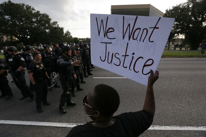 Demonstrators protest the shooting death of Alton Sterling near the headquarters of the Baton Rouge Police Department.