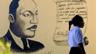 A Venezuelan girl stands in her new Bolivarian school in front of a mural with an image of U.S civil rights activist Martin Luther King before the official inauguration of this education center named in honor of King in Naiguata, 30 miles north of Caracas. The school was opened by U.S actor Danny Glover who is visiting Venezuela as a member of an Afro-American organization named 'TransAfrica Forum' which fights against the racism and for the rights of Afro descent people around the world. REUTERS/Jorge Silva  JS/GAC