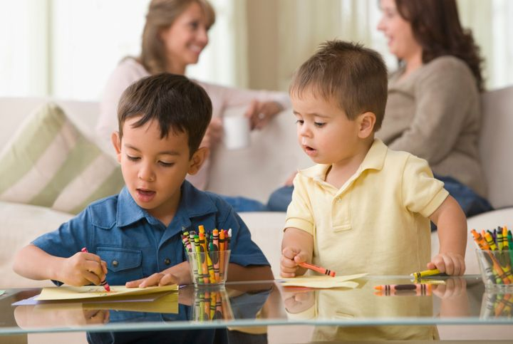 Brothers drawing together in living room KidStock via Getty Images