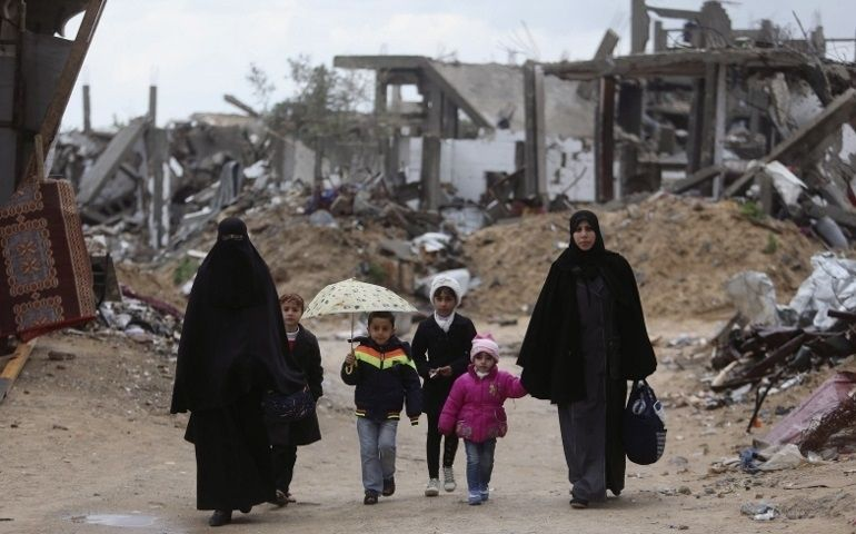 Palestinians walk near the ruins of houses that were destroyed or damaged by Israeli shelling during a 50-day war in the summ