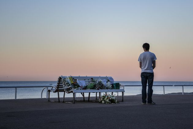 A man looks at a tribute laying on a bench near where a person was killed on the Promenade des Anglais...